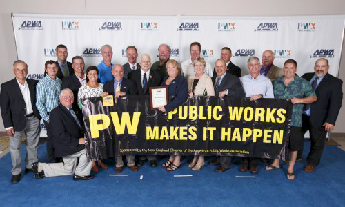Members of the APWA New England Chapter display a 'Public Works Makes It Happen banner' at a chapter event